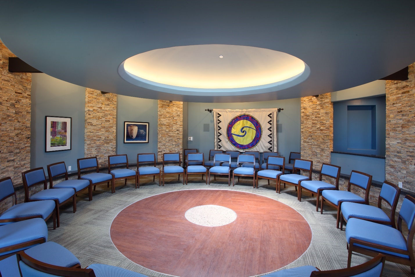 Photograph of the talking circle room at the Patina Wellness Center that has several chairs arranged in a circle with a skylight and Native American art.