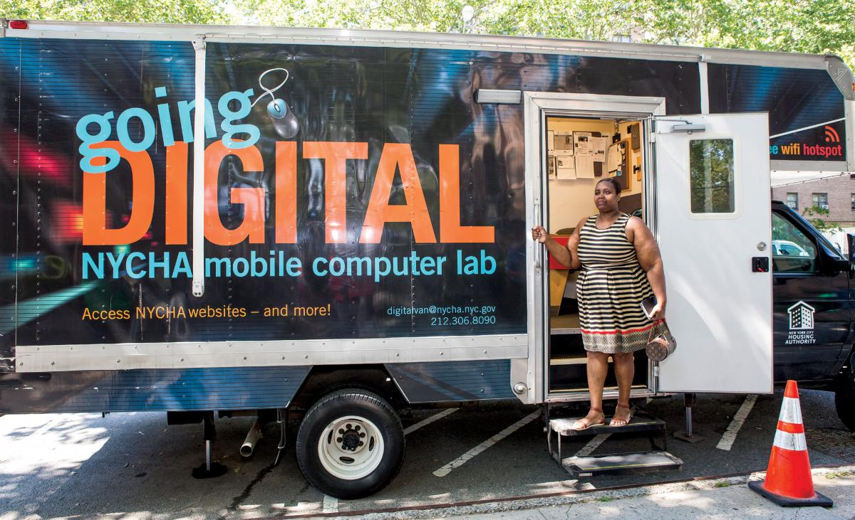A woman stands on the steps of an RV that functions as a mobile computer lab.