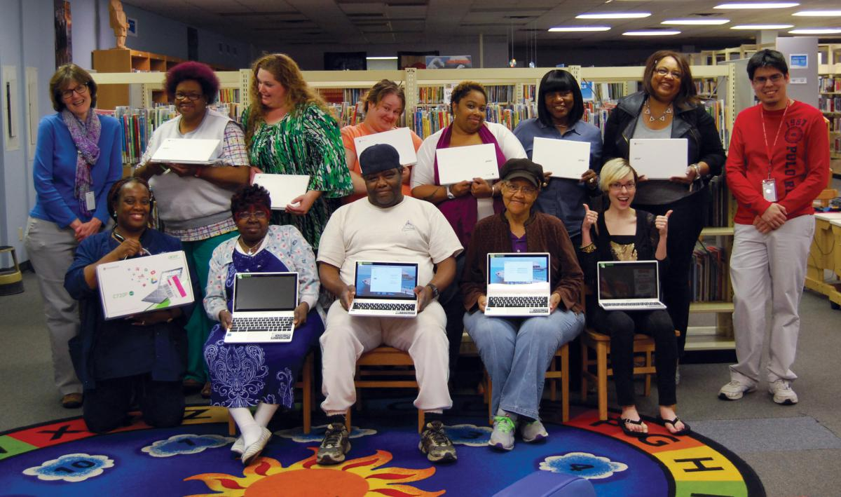 A group of men and women pose for the camera holding Chromebooks inside a library.