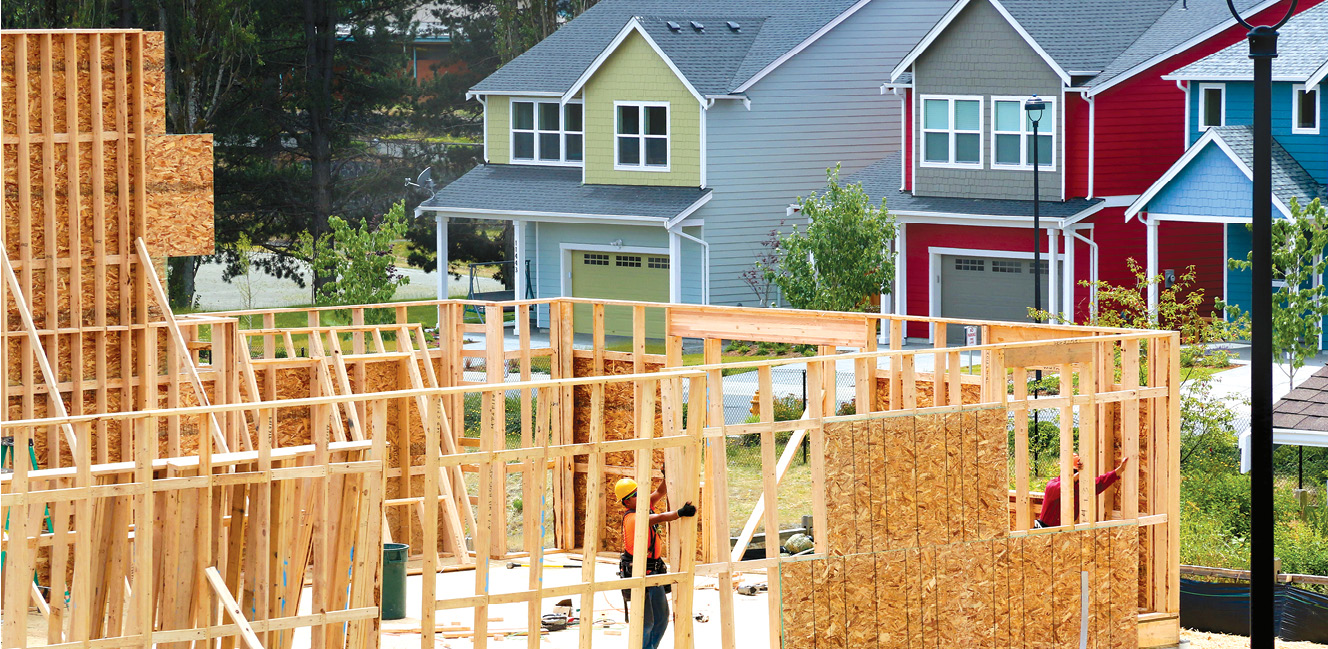 Photo shows two workers framing walls for a house under construction with two completed houses in the background.