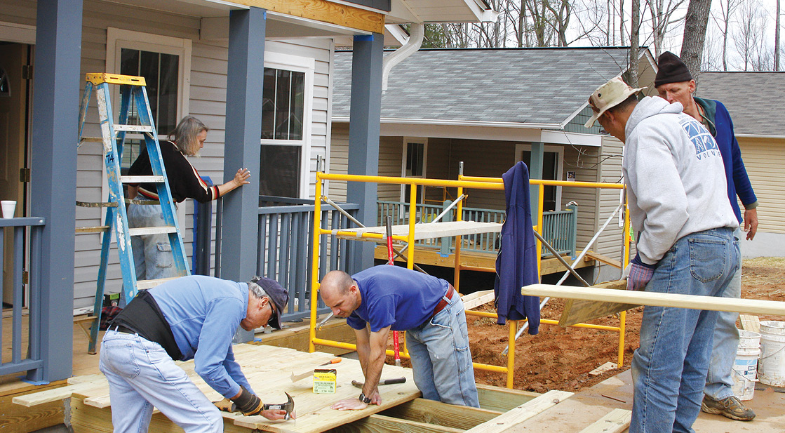 Photo shows five volunteers working on a home under construction.