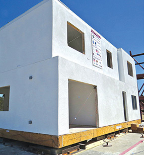 Photo shows two sides of an earthquake-resilient home with white walls and openings for doors and windows.
