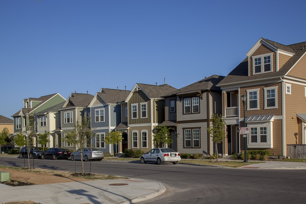 A row of closely-spaced single-family homes with three cars parked on the street.