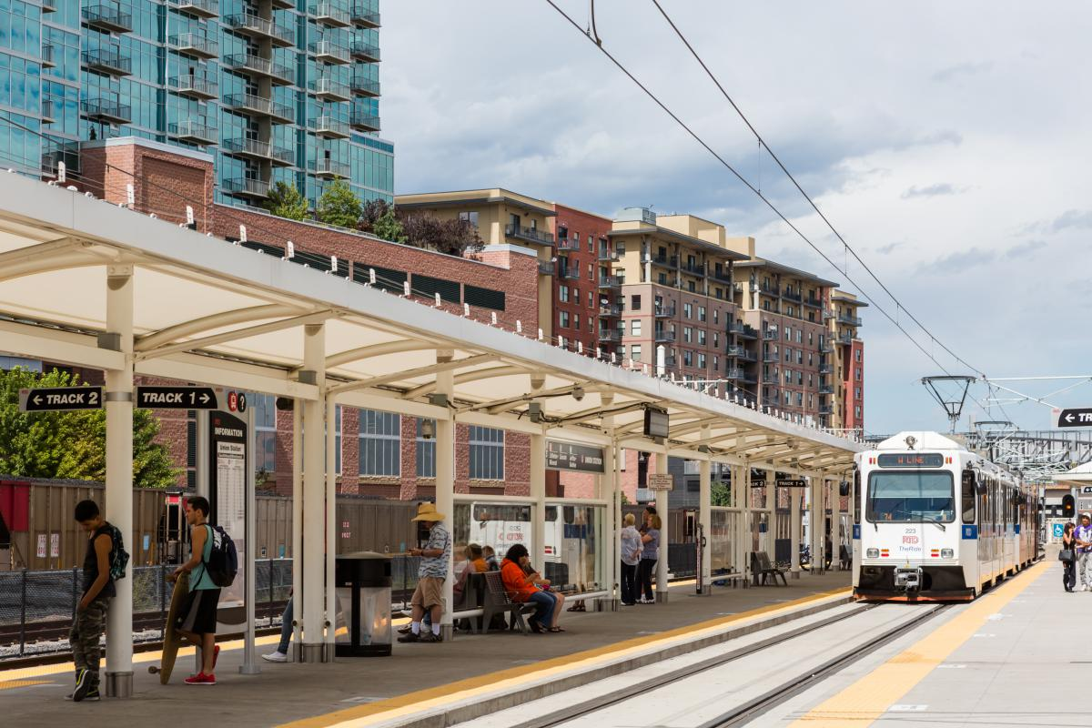 Photo shows the front of a light rail train along a covered platform with people and high rise buildings in the background.
