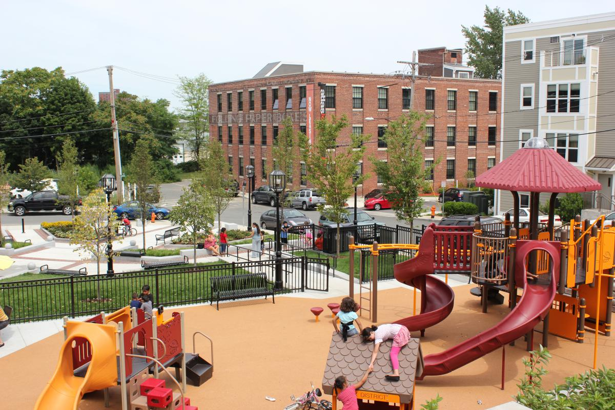 Children playing in an outdoor play area with a four-story and a three-story building in the background on the opposite side of the street.