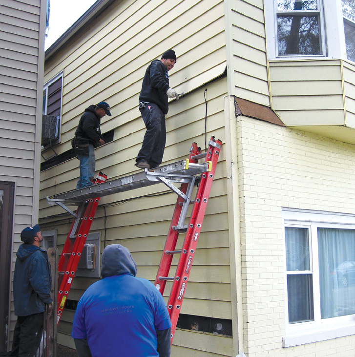 Two workers stand on a metal scaffolding plank working on the siding of a house as two others look on.