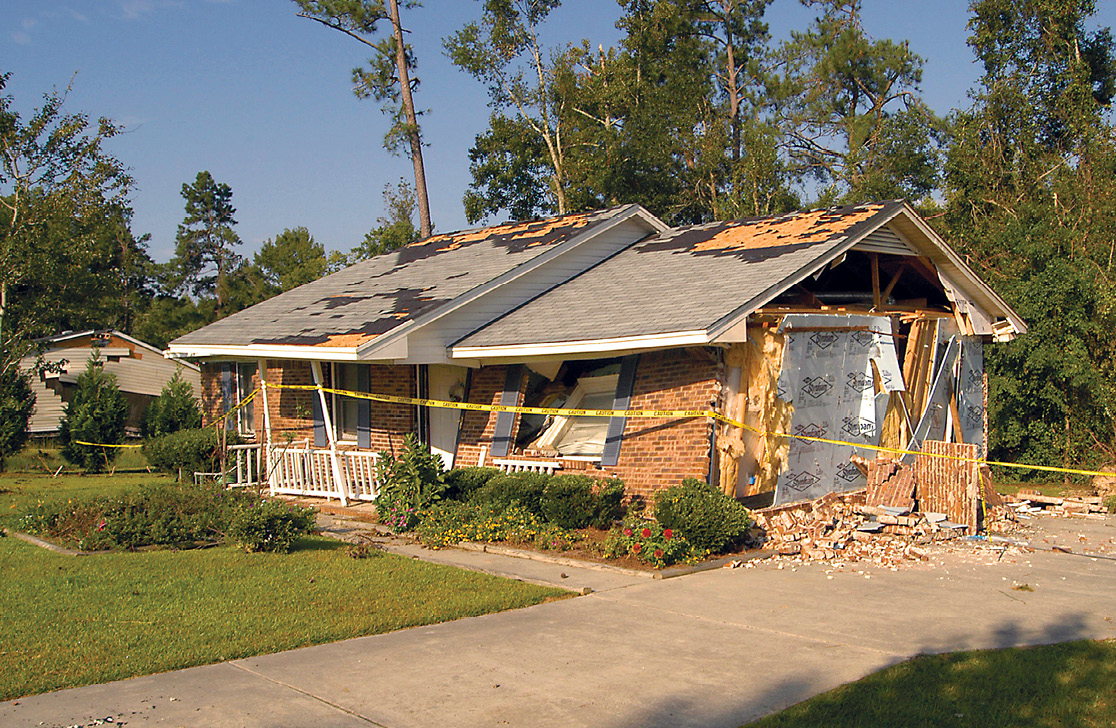 Photo shows a severely damaged single-family brick home with yellow caution tape around it.