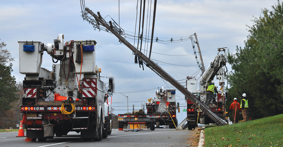 Photo shows three utility trucks and workers next to a utility pole leaning over a roadway.