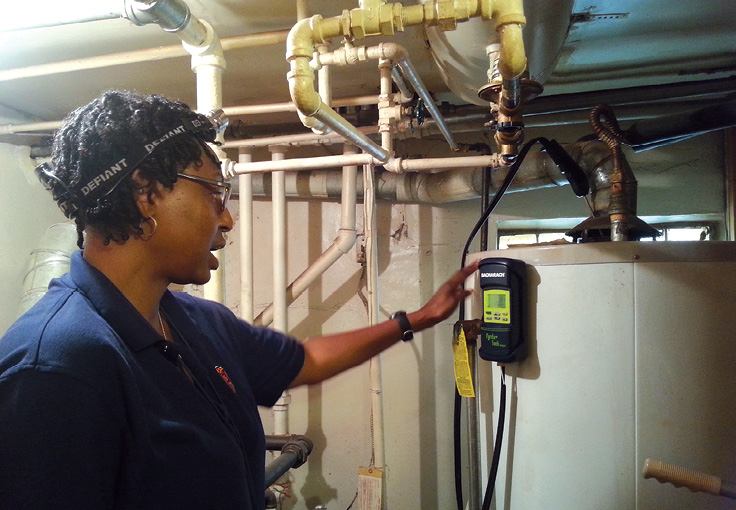 Photo shows a woman examining a hot water heater.