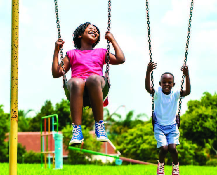 A boy and girl smile on swings in a park.