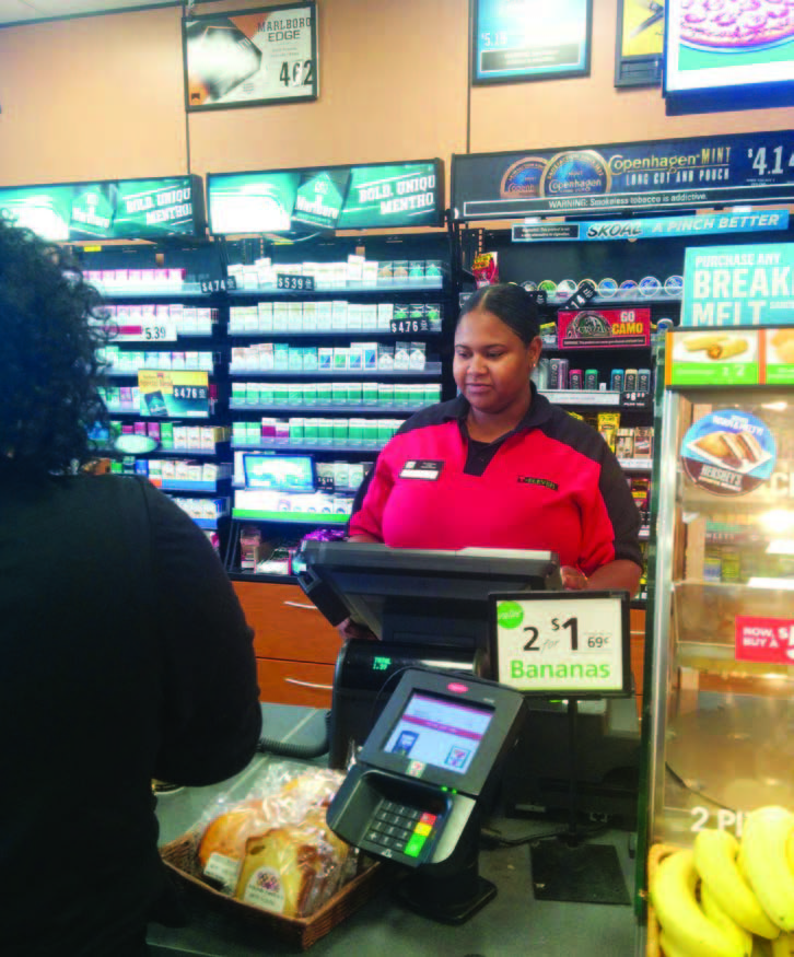A young woman behind the checkout counter of a 7-11 attends to a customer.