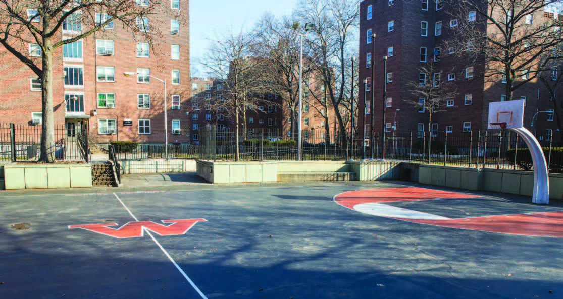 A basketball court in front of red brick apartment buildings.