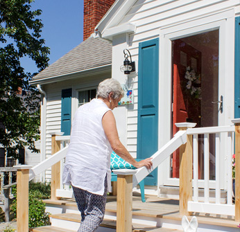 Photo shows a senior woman holding on to a railing and walking up stairs to the front stoop of a single-family home.