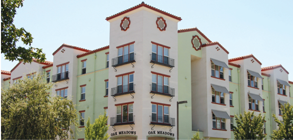"Photo shows two facades of a four-story multifamily building with two signs that read ""Oak Meadows."""