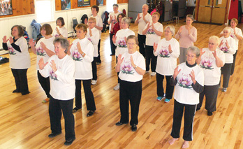 Photo shows a group of seniors standing in a room practicing Tai Chi.