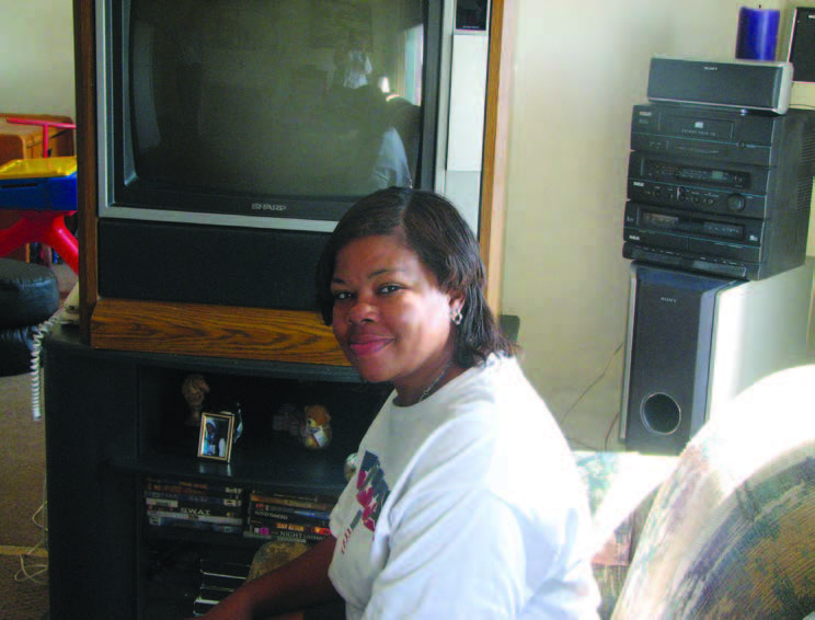 A woman seated on a sofa in front of a television.