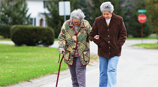 Photo shows two senior women, one of whom is using a cane, walking in a residential neighborhood.
