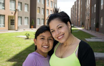 Photo of a woman and young girl smiling in the courtyard of a residential building.