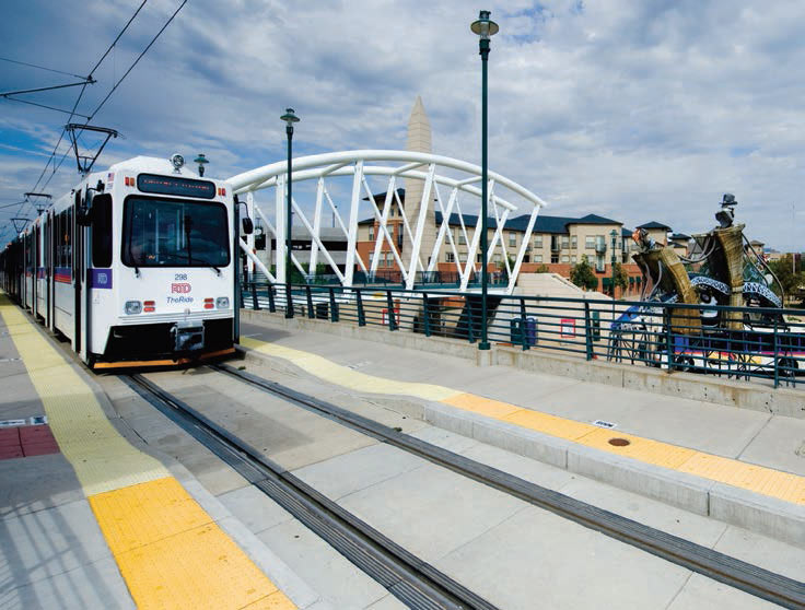 Photo shows light rail train stopped at a station in Denver.