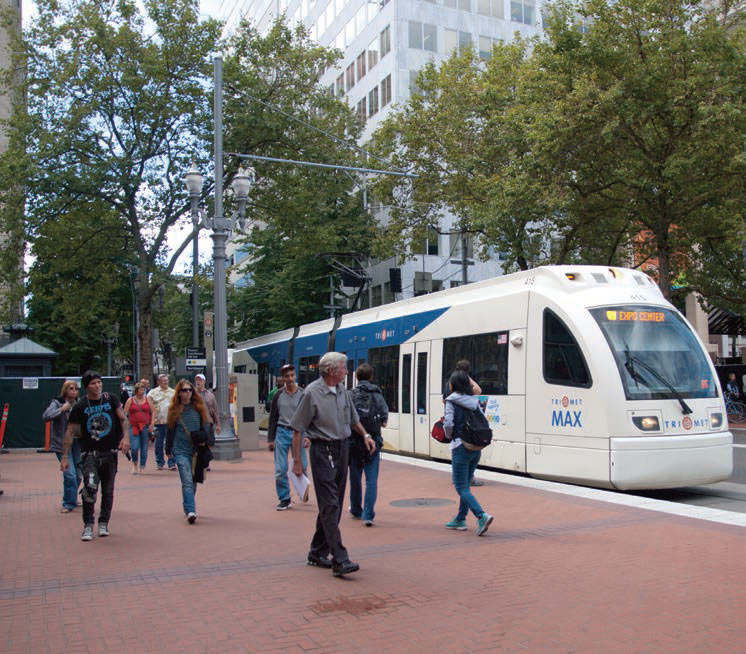 Photo shows people walking on a sidewalk with a light rail train stopped next to them.