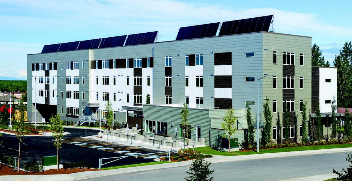 An apartment with solar panels along the roof.