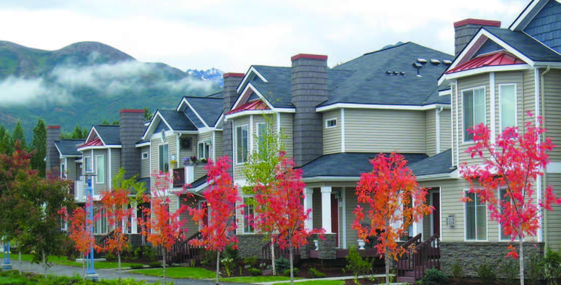 A row of homes with mountains in the background.