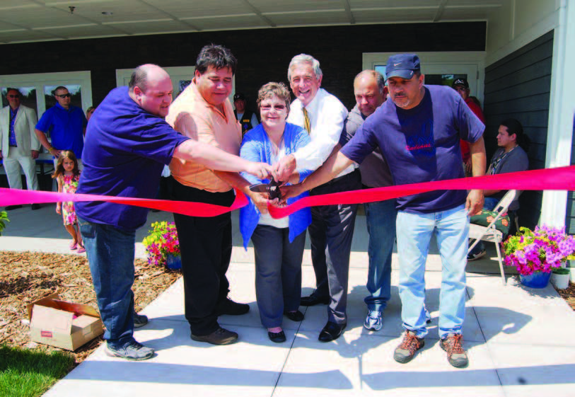 Five members of the Fond du Lac Band of Lake Superior Chippewa Indians and Rep. Rick Nolan cutting a ribbon in front of a housing development.