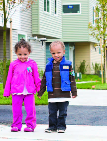A little boy and girl holding hands standing on a driveway with houses behind them.