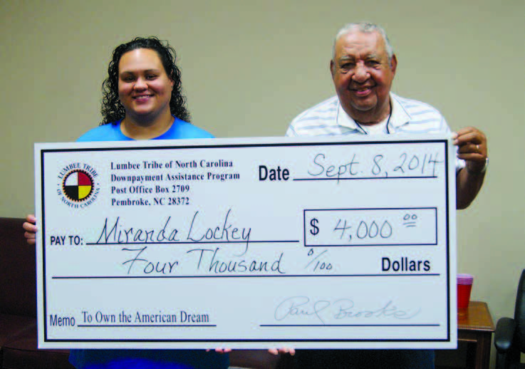 A man and woman holding a large check.