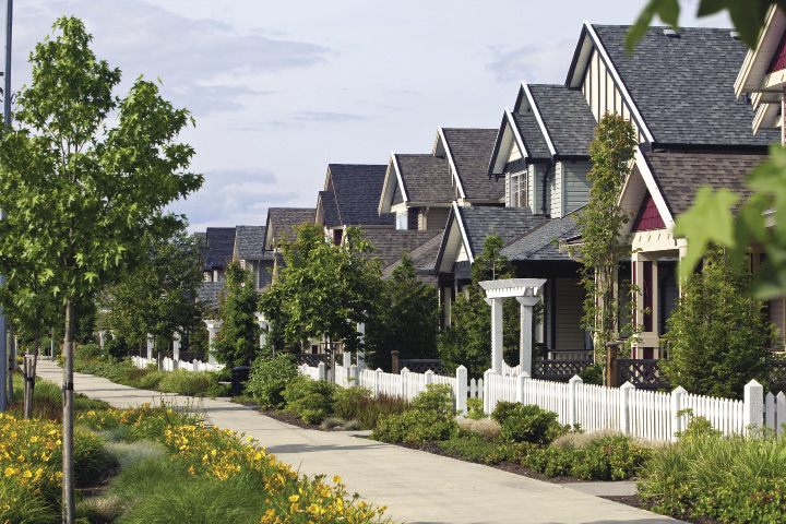 A row of single family homes with white picket fences situated close to each other.