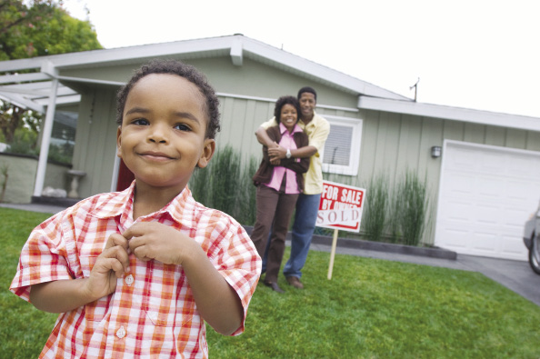 A little boy and his parents stand smiling in front of their new home.