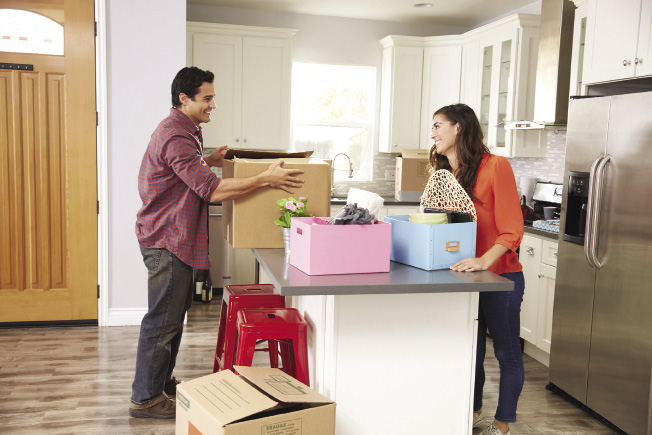 A man and woman stand on different sides of a kitchen island unpacking boxes in their home.
