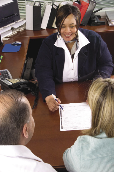 A woman explains paperwork to a couple sitting in front of her in an office.