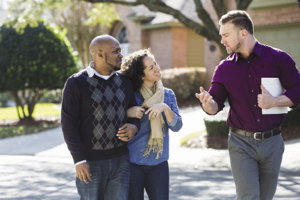 A couple listens to their realtor while walking in a residential neighborhood.