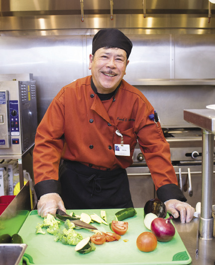Photo shows a man holding a knife to cut vegetables on a cutting board in a hospital kitchen.