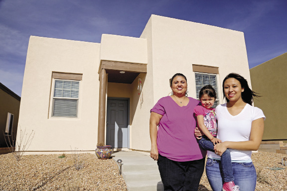 A mother and her two daughters stand in front of their new home.