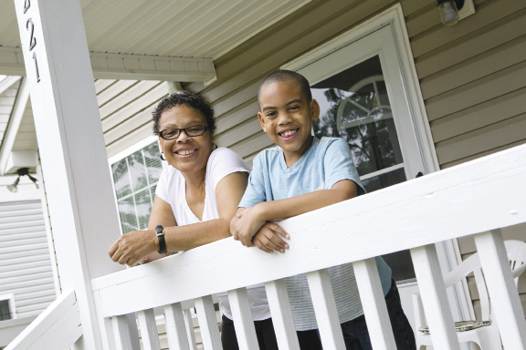 A woman and her grandson stand leaning on the railing of her home's front porch.