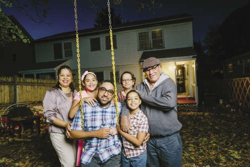 Photo shows a family of six posing in their backyard.