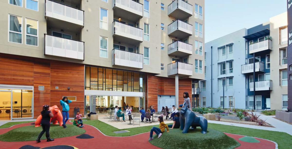 Kids in a play area situated within a courtyard surrounded by apartment buildings