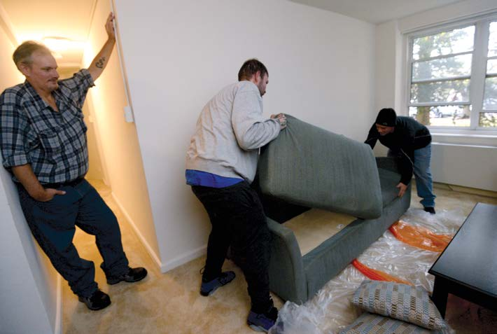 A man watches as movers assemble a sofa in his living room.