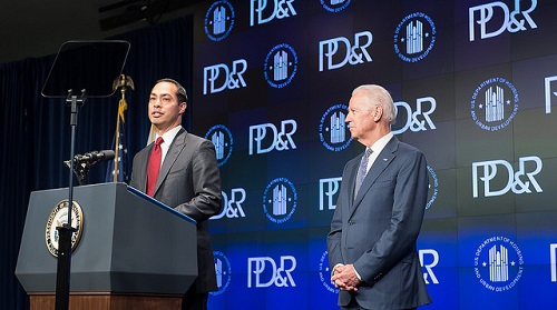Photograph of HUD Secretary Julián Castro speaking at a podium onstage, with Vice President Joe Biden standing to his left, in front of a backdrop with the HUD and PD&R logos.