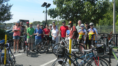 Photograph of 17 individuals, dressed in active apparel, standing next to several bicycles outside.