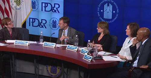 Photograph of Assistant Secretary for Policy Development and Research Katherine O'Regan and four panelists at a table on stage in front of banners displaying the HUD and PD&R logos.